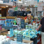 Grocer in front of their wares inside Moore Street Market