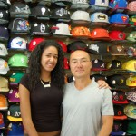 Owners of baseball cap store in front of cap wall