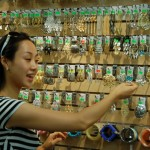 Sales person showing earrings on wall display