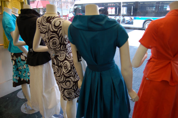 View of street behind dresses on display