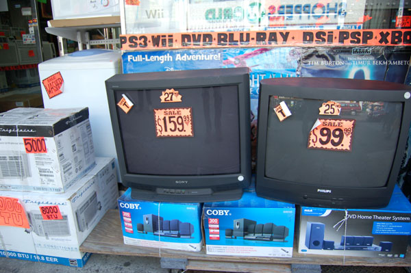Televisions, air conditioners and stereo systems for sale on outside